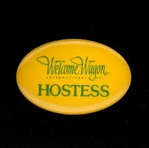 Image of Welcome Wagon Hostess Button - This item is a Welcome Wagon International, Inc. hostess' button.  Hostesses used to deliver gift baskets to new homeowners.  The button is yellow in color and has green lettering.