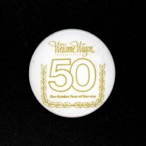 Image of Welcome Wagon Anniversary Button - This item is a button promoting Welcome Wagon International, Inc's 50th Anniversary.  It is a company that provided gift baskets to new homeowners and now sends gift books through the mail.  The button is white in color and has gold lettering.