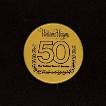 Image of Welcome Wagon Anniversary Button - This item is a button promoting Welcome Wagon International, Inc's 50th Anniversary.  It is a company that provided gift baskets to new homeowners and now sends gift books through the mail.  The button is gold in color and has black lettering.