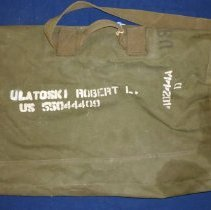 Image of United States Army Travel Bag  - This item is a travel bag used by Oak Lawn resident Robert Ulatoski while serving in the army during the Korean War.  It is green in color with white lettering and features a tag that was attached when Ulatoski was returning home.