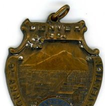 Image of Kiwanis Delegate Medal, 1924 - This item is a 1924 Kiwanis medal used by Raymond S Blunt.  The convention took place in Denver, CO, and the item is bronze in color, featuring an image of the city.