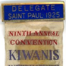 Image of Kiwanis Delegate Ribbon, 1925  - This item is a 1925 Kiwanis delegate ribbon used by Oak Lawn resident Raymond S Blunt.  The convention took place in Saint Paul, and the item is tan in color, featuring  an image of a man fishing.