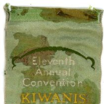 Image of Kiwanis Delegate Ribbon, 1927 - This item is a 1927 Kiwanis delegate ribbon used by Oak Lawn resident Raymond S Blunt.  The convention took place in Memphis, and the item is green in color, featuring  an image of a white flower.