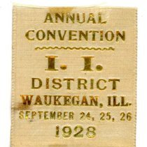 Image of Kiwanis Delegate Ribbon, 1928 - This item is a 1928 Kiwanis delegate ribbon used by Oak Lawn resident Raymond S Blunt.  The convention took place in Waukegan, IL, and the item is tan in color with gold lettering.