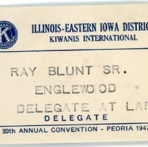 Image of Kiwanis Delegate Pin, 1947 - This item is a 1947 Kiwanis delegate pin used by Oak Lawn resident Raymond S Blunt. The convention took place in Peoria, and the item is white in color with blue lettering.