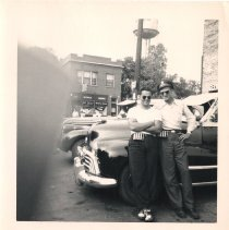 Image of 95th Street and Cook Avenue - This is a photograph of 95th Street near Cook Avenue in the 1940s.  The two gentleman in the photo are unidentified, and visible in the background are the Oak Lawn Water Tower and the former Schultz's Store.
