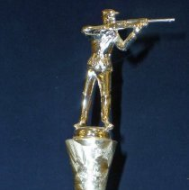 Image of Frankfort Sportsman's Club Trophy, 1964 - This item is a 3rd place trophy from the 1964 Frankfort Sportsman's Club event.  Richard Hanson, who held the trophy, attended the contest with other members of the Oak Lawn Sportsmen's Club.  It features a small statue at the top depicting a hunter holding his weapon.  The club was located at 107th Street and Central Avenue in Oak Lawn.