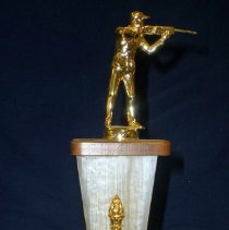Image of Cook County Council Trap Shoot Trophy, 1966 - This item is a 1st place trophy from the 1966 Cook County Council Trap Shoot event.  Richard Hanson, who held the trophy, attended the contest with other members of the Oak Lawn Sportsmen's Club.  It features a small statue at the top depicting a hunter holding his weapon.  The club was located at 107th Street and Central Avenue in Oak Lawn.