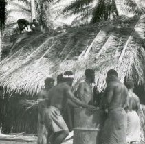 Image of World War II Photograph - This is a photograph taken in the Pacific Theater during the Second World War. It features a group of native men standing in front of a hut, and may have been snapped in the Philippine Islands.
