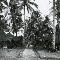 Image of World War II Photograph - This is a photograph taken in the Pacific Theater during the Second World War. It features a man walking down a path between a row of tents, and may have been snapped in the Philippine Islands.
