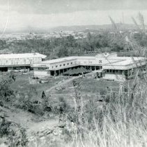 Image of World War II Photograph - This is a photograph taken in the Pacific Theater during the Second World War. It features a few large buildings with grasses in the foreground, and may have been snapped in the Philippine Islands.