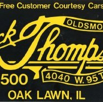 Image of Jack Thompson Oldsmobile Promotional License - This item is a promotional license plate used by Jack Thompson Oldsmobile located at 4040 west 95th Street in Oak Lawn.  It is yellow and black in color with promotional emblems and slogans.