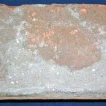 Image of Brick from St. Gerald Church and School - This item is a brick from St. Gerald church and school collected after the 1967 tornado.  It is red in color and still has pieces of cement attached.