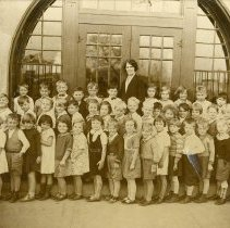 Image of 1932 Cook School First Grade Class Photograph  - This is a photograph of Cook School's first grade class in 1932.  Teacher Mrs. (Whitehill) Larson is standing in the very back, while in the first row, sixth from the left, Rhoda (Zuschlag) Powers is visible.  In the second row Frank Roebuck is standing fourth from the left, and Lois Prange is standing seventh from the right.