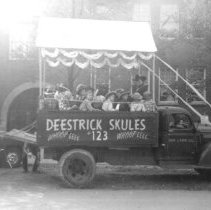 "Image of Round-Up Parade Float ""Deestrick 123 Skules"" - This is a photograph showing the Round-Up float ""Deestrick 123 Skules"".  A number of children are sitting in the back of the truck."