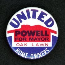 Image of United Homeowners Party Campaign Pin - This item is a 1973 campaign pin for the United Homeowners Party led by Dr. Thomas Powell. It is blue, white, and red in color and features the image of a home. Initially declared the winner, Powell would relinquish the mayor's office after just four months when the original results were overturned.
