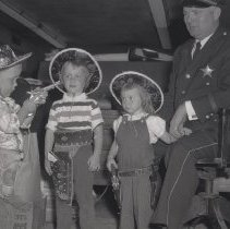 Image of Oak Lawn Round-Up - This item is a film negative displaying the 1958 Oak Lawn Round-Up.  From left to right are Artie Haggerty, Phyllis Haggerty, Kim Vandermeer, and Chief of Police Robert Jelley.  This was the last year the Round-Up was held.