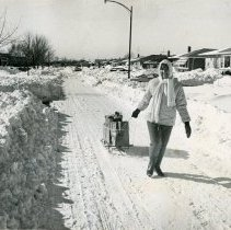 Image of 1967 Snowstorm - This is a photograph of the 1967 Snowstorm which blanketed the Chicago area, including Oak Lawn, with several feet of snow.  It features a women pulling groceries on a 103rd Street near Cicero Avenue.