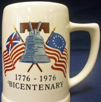 """Image of American Bicentennial Mug - This item is a promotional mug produced for the 1976 American Bicentennial celebration.  The mug is white in color and features an image of the Liberty Bell and flags on the front.  That year, Oak Lawn held a """"67 in 76"""" event that commemorated the village's anniversary as well.  These mugs were sold as part of the combined celebration."""