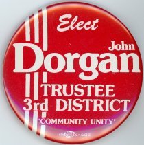 """Image of John Dorgan Campaign Pin - This item is a campaign pin for John Dorgan, a trustee candidate for the 3rd district.  It is red and white in color and features the slogan """"Community Unity""""."""