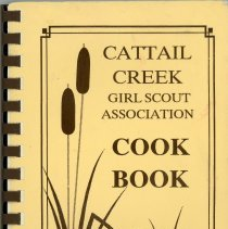 Image of Cattail Creek Girl Scout Association Cookbook - This item is a cookbook compiled by the Cattail Creek Girl Scout Association. Located in southern Cook County.  This organization was celebrating their 20th anniversary in 1997. The cover features an image of cattail plants and is cream in color.