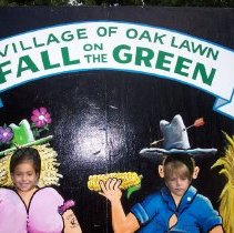 Image of 2009 Fall on the Green - This is a photograph of the 2009 Oak Lawn Fall on the Green celebration.  It features several children posed in a photo display.