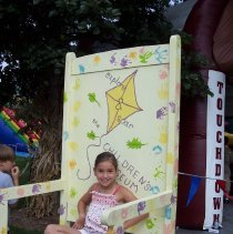 Image of 2009 Fall on the Green - This is a photograph of the 2009 Oak Lawn Fall on the Green celebration.  It features a child sitting on a large painted rocking chair.
