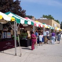 Image of 2009 Fall on the Green - This is a photograph of the 2009 Oak Lawn Fall on the Green celebration.  It features people walking between the stalls of local businesses.