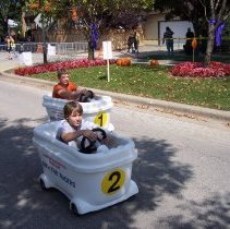 Image of 2009 Fall on the Green - This is a photograph of the 2009 Oak Lawn Fall on the Green celebration.  It features children riding in Bath Tub Racers.