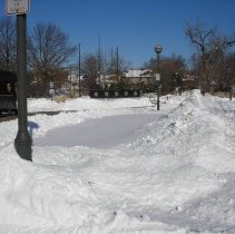 Image of 2011 Snow Storm - This is a photograph of the 2011 snow storm that struck the Chicagoland area.  It features a parking lot and the village green with a cover of snow. The Veteran's Memorial is visible.