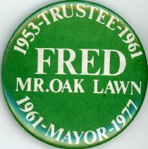 "Image of Fred M. Dumke Promotional Pin - This item is a pin used to promote the former Oak Lawn mayor and trustee Fred M. Dumke.  It is green in color with white lettering and gives Dumke the title of ""Mr. Oak Lawn""."