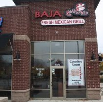 """Image of 95th Street Oak Lawn - This is a photograph of Baja California Fresh Mexican Grill and Northern Border American Grill located on 95th Street and 53rd Avenue.  A sign in the window advertises a new restaurant, Stacked, """"coming soon."""""""