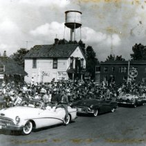 Image of Oak Lawn Round-Up Days - This is a photograph of the Round-Up parade on 95th Street near Cook Avenue.  It features several cars in the parade and a large group of spectators.  A few businesses and the old water tower can be seen in the background.