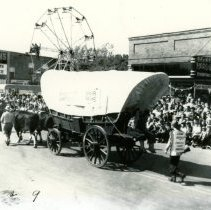 Image of Oak Lawn Round-Up Days - This is a photograph of the Round-Up parade on 95th Street near Raymond Avenue. It features people dressed in cowboy attire riding an oxen drawn wagon. Stevens and Co. Real Estate and Insurance, a ferris wheel, and Behrend's Hardware can be seen in the background.