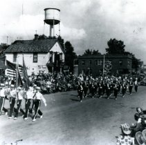 Image of Oak Lawn Round-Up Days - This is a photograph of the Round-Up parade on 95th Street near Cook Avenue.  It features a marching band and flag carriers at the front.  A few businesses, including the Sinclair Service Station, and the old water tower can be seen in the background.