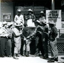 Image of Oak Lawn Round-Up Days - This is a photograph of the Round-Up Days in Oak Lawn. It features an enactment of a criminal on trial. His hands are bound and a noose already hangs around his neck as Judge Roy Bean issues his sentence.