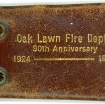 Image of Fire Department Key Holder - This item is a key holder from 1954 advertising the Oak Lawn Fire Department's 30th Anniversary.  It is brown in color with gold lettering and is held closed with a snap button. At the time the department was a volunteer organization.