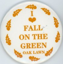 Image of Fall On The Green Promotional Pin - This item is a Fall On The Green promotional pin.  It is white in color with brown lettering and leaf images on the exterior.