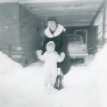 Image of 1967 Snowstorm - This is a photograph of the 1967 Snowstorm which blanketed the Chicago area, including Oak Lawn, with several feet of snow.  It was taken from 8736 South Sproat Avenue and features Helen Alstrom and a child enjoying the snow.