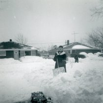 Image of 1967 Snowstorm - This is a photograph of the 1967 Snowstorm which blanketed the Chicago area, including Oak Lawn, with several feet of snow.  It was taken at 8736 South Sproat Avenue and features Helen Alstrom shovelling snow.  Ray Owens is visible in the background.