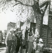"Image of Oak Lawn Round Up Days - Lynch Mob - This is a photograph of various participants involved with an Oak Lawn Round-Up reenactment. This scene depicts a ""lynch mob"" hanging a thief.  McKay's Ladies Wear is visible in the background.  During the event, many participants would dress up on Western style clothing and play different characters."