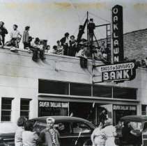 Image of Oak Lawn Round-Up Days - This is a photograph of spectators watching the 1952 Round-Up parade from the roof of the Oak Lawn Trust and Savings Bank, located near 95th Street and 53rd Court.  The bank merged with the First National Bank of Evergreen Park in 1992 and no longer exists today.