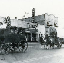 Image of Oak Lawn Round-Up Days - This is a photograph of the Round-Up parade on 95th Street near 53rd Court. It features people dressed in cowboy attire riding horse drawn carriages and wagons. Oak Lawn Trust and Savings Bank can be seen in the background.