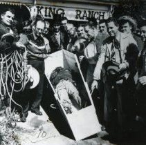 Image of Oak Lawn Round-Up Days - This is a photograph of the Round-Up Days in Oak Lawn. It features a reenactment of a criminal after he was tried, hung, and placed in a casket.  A group of men gather around the dead man and, on the left, a small boy watches.