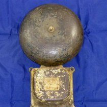 Image of Cook Avenue School Bell - This item is an electric bell from the former Cook Avenue School. It is unknown when the bell was installed or what part of the building it came from. It may have been used outside, as there is considerable wear to the item. The bell is divided into two separate pieces.
