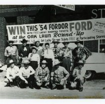 "Image of Oak Lawn Round-Up Days - This is a photograph of the Round-Up Days in Oak Lawn. A raffle was held in which the winner would receive a '54 ""Fordor Ford"".  The photo features men and women dressed in cowboy attire posing in front of the car."