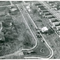 Image of Aerial Photograph of Briggs Otto Place - This is an aerial photograph showing a view of several structures including Briggs Otto Place (believed to be on the left).  Work is in progress on a home (installing water service) and the new street has several vacant lots.