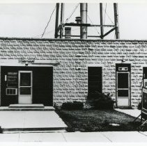 Image of Village Hall - Photograph of the Oak Lawn Village Hall and Police Station in 1948. This structure was located on Cook Avenue near 95th Street. There is a United States Marine recruitment poster visible on the right.