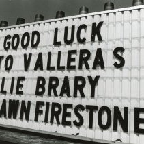 """Image of Signboard for grand opening of Lie-Brary Tavern - Photograph of a sign for the grand opening of the """"Lie-Brary"""" Tavern and other businesses in 1974. This building was named after a conflict with the Oak Lawn Public Library. The sign also mentions Vallera's and Firestone."""