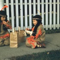 Image of Twin Sisters at Halloween  - Twin sisters eating their Halloween candy while trick-or-treating. The girls are related to Ray Eldridge, a business owner in the Oak Lawn Community.  The costumes were hand-made by Mary Eldridge.